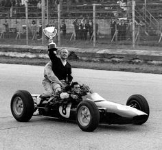 Colin Chapman and the mechanic hopped on the back of Jim Clark's Lotus after winning the World Championship. Chapman was one of the most passionate personalities in motor racing and was always a fixture at the finish line. Quite often, running on to the track, to applauded his driver as one of his cars took the chequered flag.
