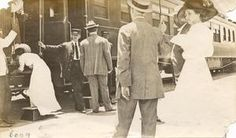 of two women wearing long dresses and large hats, two men in suits and hats, a black porter and two conductors (one black and one white) stand near a stationary train. Austin Texas, ~1900