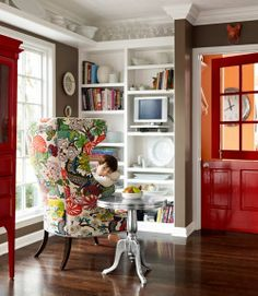 I love this room, the wood flooring, the built ins, the used shelf that runs the ceiling and red doors. I love red doors. Note the brown wall :) and the little piggy knocker up above! What a whimsical touch. Happy room.