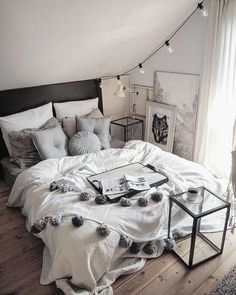 Such a beautiful bedroom! The soft grayscale of the bedding, the cute pom poms on the covers, and the cool lights are all fantastic. I would love to have this bedroom!