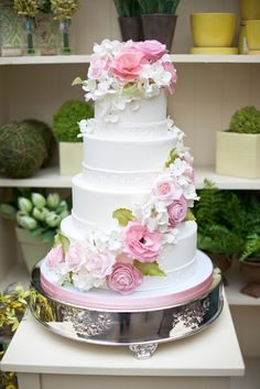 Ivory wedding cake with garlands of pink flowers and accents of green.  Great for a spring wedding!