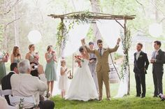 rustic arbor made with branches and willow, some wispy greenery and flowers