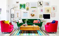 Dark green velvet sofa with hot pink velvet chairs and a colorful striped rug