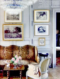 Leopard sofa love. Layered art on top of paneled walls // living room