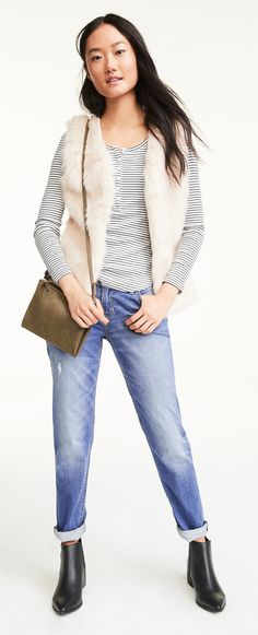 Mixing textures and shapes turns an outfit interesting. Pair a fuzzy vegan fur vest with a thin, silky henley underneath. And since the name of the game is contrast — your slouchy boyfriend denim belongs with pointed, leg-lengthening booties.