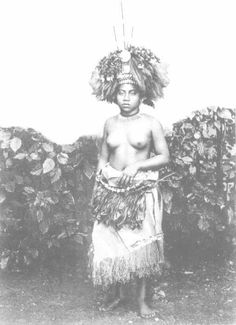 A village maiden (taupou) in festive attire. She wears the head dress tuiga, compsed of four parts, the three sticks (lave), the ornementation of red parrot feathers ('ie ula), the hair decoration (lauulu) made of bleached human hair, and the forhead ornamentation of nautilus shells (pale fuiono). Around her neck she has a collar of small sperm whale teeth (ulalei) and around ner body are some fine mats ('ie toga) covered by a klit of ti-leaves (titi) such as were formerly worn on the naked…