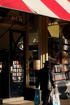 man standing beside bookstore facade