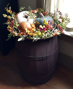Trio of colourful pumpkins atop a wine barrel, sprigs of seasonal berries and hips, leaves