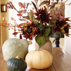 Pumpkins and gourds complement an urn filled with an autumnal arrangement of red sunflowers, berries and leaves.