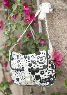 """The very useful """"Veronika"""" bag was inspired by old-time schoolbags. Practical flap and adjustable shoulder strap. The beautiful pattern is printed on heavy cotton canvas and lined in a sprightly polka dot print."""