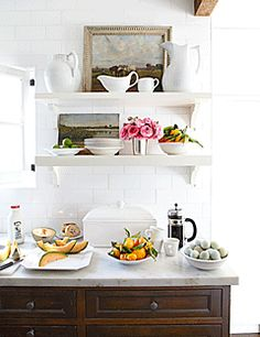 "Traditional upper cabinets can close off a kitchen. By installing open shelves, designer Chris Barrett made her small California kitchen seem more open. ""Wall cabinets are utilitarian but so dull. I love having open shelves and being able to stack pretty dishes and paintings on them,"" she says."