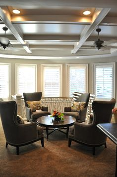 The upstairs family room slash media room featured a curved wall of windows, a beamed ceiling...
