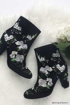 A pair of faux suede boots featuring embroidered floral detailing, a side zip closure, and a chunky heel.