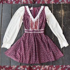 Embrace the Fall with this gorgeous Gunne Sax dress! Burgundy floral pattern mixed with lace trim, lace up front detail, and satin ribbon trim around the waist. Sleeves are sheer cream cotton and it t