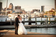 Bride and Groom hugging by the pier dock on the harbor with Baltimore City view. Baltimore Museum of Industry wedding photos by photographers of Leo Dj Photography. http://leodjphoto.com