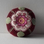 Handmade Pin Cushion Felted Wool Wild Rose - 2 1/2 H x 3 1/2 W. Felted wool applique with pearl cotton embroidery makes me think of summer nights. I love the big flower in two shades of pink with its yellow center. All this appliqued onto a brown tweed felted wool pin cushion. I stuffed this pin cushion with fiberfil. Button tufted with a yellow button on the top and a dark brown button on the bottom. I didnt put this pin cushion into a container because sometimes a pincushion just needs to…