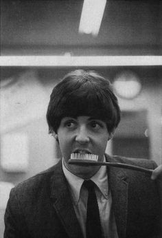 Paul McCartney brushing his teeth with a giant toothbrush.