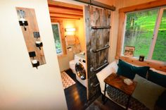 cool barn door to bathroom is also ladder to loft space. 224-sq-ft-tiny-house-on-wheels-11