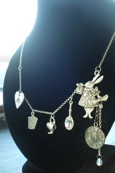 Asymmetrical necklace with the center piece on the side. The white rabbit, with his pocket watch, and small blue crystal for alice. The necklace include a hand mirror charm, teapot charm, card charm, and queen of hearts charm. Antiqued silver plated necklace. Charms are silver plated, antiqued silver, and gunmetal grey.