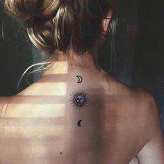 Um personificada sol fica entre um par de luas crescentes em volta da tatuagem.