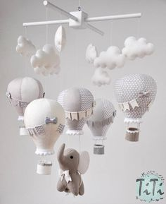 Personalized elephant and balloons baby mobile in custom colors. This item contains 1 handmade felt elphant , 5 handmade hot air balloons, 8 handmade felt clouds and wood mobile in white color. The balloons are decorated with pompons, bunting flags and and little baskets. Perfect as a