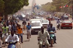 Typical street scene in Ouagadougou, Burkina Faso. Shows the well-known Place des Nations Unies (United Nations Square). The flags on the right mark the entrance to the main FESPACO building.