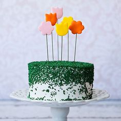 Ooh and aah party guests with this spring sprinkle cake. Tall flower toppers add showstopping height to this centerpiece cake./