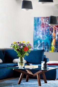 Fragment salonu nasyconego soczystymi kolorami mebli, sztuki i natury.
