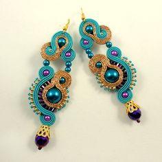 Bollywoodzki poranek – to kolczyki wykonane pracochłonną techniką haftu sutasz w kolorach złota i turkusu z dodatkiem fioletu. Szklane kryształki, koraliki i perełki pięknie się komponują w towarzystwie jedwabnych sznurków sutasz. Bigle antyalergiczne.