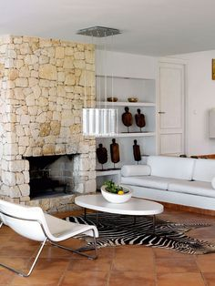 The impressive, rustic fireplace in sandstone, the African wooden sculptures and the and zebra skin bring nature into the living room, where the white minimalist furniture creates both calm and contrast.