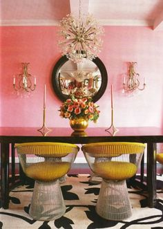 A Divine Dining Room. In yellow Platner chairs around a glossy black table in the glow of pretty pink walls. Interior Design: Betsey Johnson for her New York home.