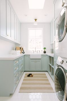 Blue green u-shaped laundry room boasts a beige striped rug placed on white hex floor tiles beneath a skylight. Blue green u-shaped laundry room boasts a beige striped rug placed on white hex floor tiles beneath a skylight.