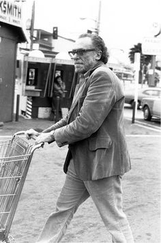 Bukowski pushing a shopping cart through a parking lot with style and aplomb