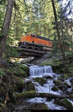 """An eastbound BNSF Q train passes over a beautiful waterfall east of Skykomish, WA just after passing over the Foss River Trestle.""--Would you climb up underneath this bridge? Would you stay when a train came?"