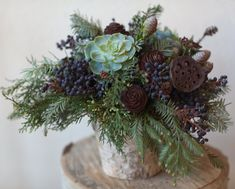 A Christmas arrangement of succulents, evergreens, cones and berries by Journal.florali.com.