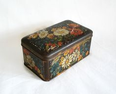 Vintage hinged tin box featuring floral graphics with daisies and other colorful spring flowers. Shabby tin measures 6 x 3 1/2 (15 x 9 cm) by 2