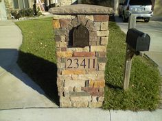 Stone mailbox. attrctive brick color selection and arrangement and a quaint brick arch around the iron mailbox inset