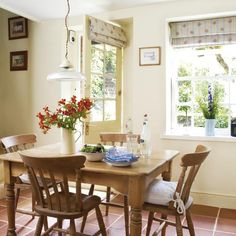 Country cottage dining room. A beautiful terracotta floor adds real warmth to this country cottage-style dining room, and contrasts well with the buttery cream walls. A chunky cream jug with flowers makes for a pretty centrepiece on the rustic dining table, while subtly floral blinds add interest to the windows.