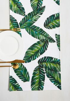 Bring a piece of paradise to your home with this tropical table runner, and you'll be the go-to hostess for gorgeous fetes! Printed with a collage of rich green palms, this woven white textile is always ready to entertain and enchant - just like you!By the way, this lovely item will be available for purchase in May!