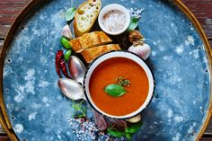 #Tomato soup Gazpacho  Rustic wooden table with tomato soup Gazpacho in rustic metal bowl fresh baguette chili garlic and basill on old rusty iron background top view copy space.