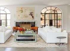 Two arched windows frame the fireplace and a painting by Terrell James, and set the stage for the perfect symmetry of hockey star Jason Arnott's living room.   Photographer: Nathan Schroder   Designer: Lloyd Ralphs Design