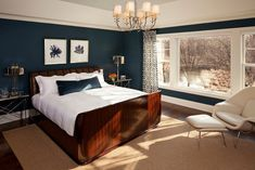 Tiefblau auf Wände schaffen eine elegante und dramatischen Flair dieser weißen getrimmte Hauptschlafzimmer Foto von Martha O'Hara Innenräume