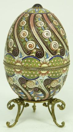 RUSSIAN SILVER ENAMELED AND JEWELED EGG BOX      Russian silver egg box having a multicolor enameled spiral design. Round cabochon ruby set to top. Gold wash interior. Holds double headed eagle mark, 84 silver purity with town mark and Ivan Petrovich Khlebnikov workmaster marks
