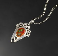 An Art Nouveau silver pendant designed by Archibald Knox for Liberty & Co, the Celtic shield design with a central panel of red and green en...