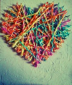 DIY colored yarn tangled around nails, nailed in a heart shape on a piece of painted plywood. :)