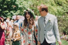 bride in floral dress and flower gown walks with groom in linen jacket @myweddingdotcom