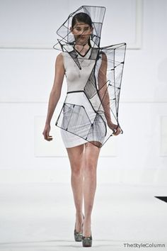 Wearable Architecture - sculptural fashion; experimental 3D fashion construction // Richard Sun. A simple array of body con dresses were pieced together with monochrome inserts and black piping to form geometric shapes criss-crossing over the body. Each garment was accessorised with a mesh and metal construction which closed around the bodies and faces of the models. These structures were inspired by an empty shell of a Hong Kong building which was surrounded by metal bars.