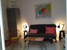 Salon, canapé-lit Ikéa, vestiaire métallique industriel, fauteuil rotin, table pied en fer et carte scolaire vintage