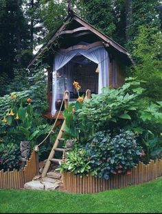 playhouse... (I love how it is raised off the ground, but not actually built into a tree. I also love how it is surrounded by plants and trees....Oh, and it's so pretty too!!! I think I know someone who could build this!!)