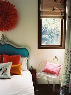 lovely and perfect bedroom--blue headboard, bright pillows + acrylic chair.